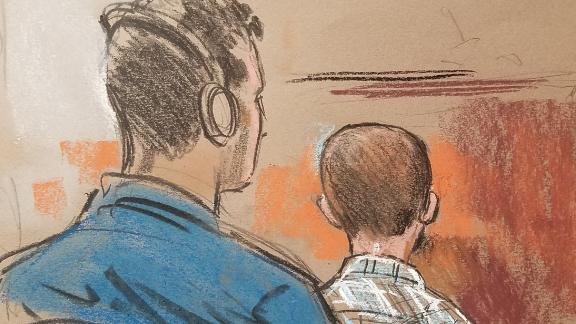 6-year-old boy, Rodolfo, the youngest  child in court this day, sits on his father's lap. As he did with most of the children, Judge Bryant asked Rodolfo if he was in school, translated by an interpreter via headphones provided to every immigrant facing the court.