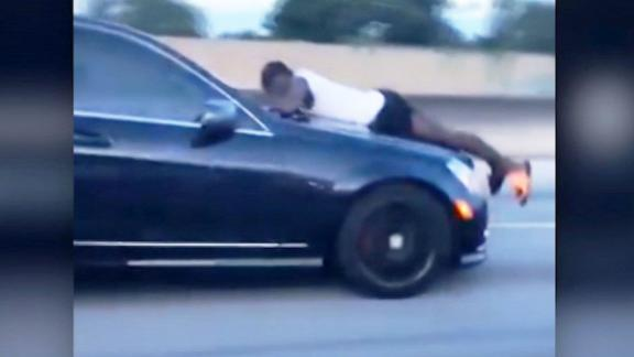 """Man clinging to hood of car doing 70 mph calls 911. CNN's Jeanne Moos has the tapes.       Hood Hanger 911   Maybe you've seen the amazing vid of the guy clinging to the hood of a Mercedes doing 70 mph on the interstate in Miami. He was using one hand to hang on and holding the phone in the other. It went viral but no one knew the whole story till now. It's a doozy. While clinging to the car the guy called 911 (""""I'm on top of a speeding vehicle! OK, what's the address?""""). Turns out the woman driving was his ex from a rocky relationship. They argued over who was going to use the car and when she got in to go pick up her daughter, he jumped on the hood. She drove 15 miles (!!!!!) down the interstate with him hanging on for dear life. Eventually she pulled over (she shot video of his face through the windshield yelling """"get off of my car"""" and another motorist captured the vid of the guy hanging on from the neighboring lane). Police came and arrested her, charged her with culpable negligence. We have sound with both the woman and the guy. She says he's an ex who won't leave her alone. His final bite...""""just watch yourself and be careful who you  love."""" I did a pretty unusual standup lying on the hood of a crew car while the photog shot me from inside the car.  We did not drive during the standup but Time Warner security came up to say they'd gotten 5 calls from concerned citizens."""