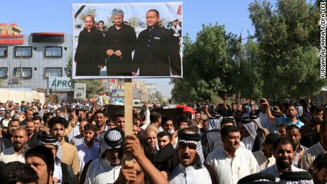 Iraqis carry a picture of some of the victims during a funeral procession in Karbala city Thursday.