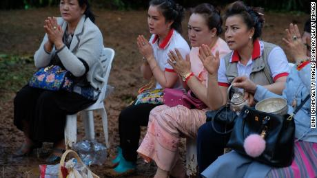 Buddhist followers pray at the entrance of Tham Luang Nang Non caves in the hope of finding the boys alive.