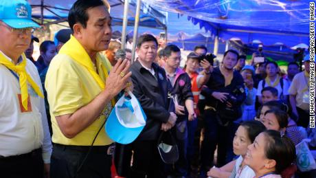 Thai Prime Minister Prayut Chan-O-Cha speaks with family members of the missing children and their coaches on Friday.