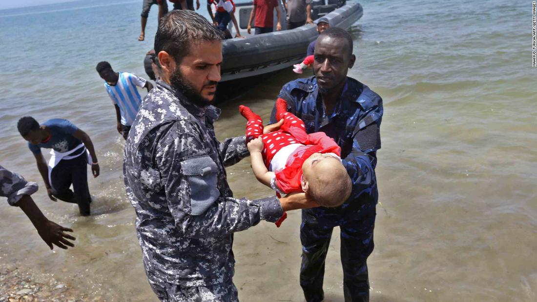 Survivors arrive on shore as two men hold the body of one of the three babies.