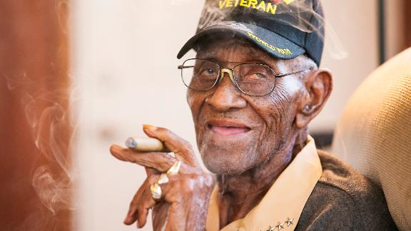 Richard Overton, the oldest living U.S. Veteran at the age of 111, is back in the east Austin home he has owned since 1948 after a renovation provided by Meals on Wheels of Central Texas and the Home Depot Foundation. He greets guests as he enjoys a cigar in the back living room, his favorite room in the house. (Ralph Barrera/Austin American-Statesman via AP)