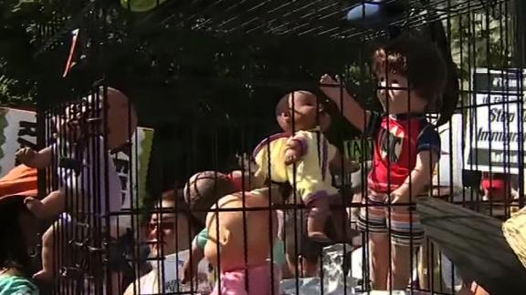 Protesters in Atlanta are carrying a dog crate with baby dolls inside