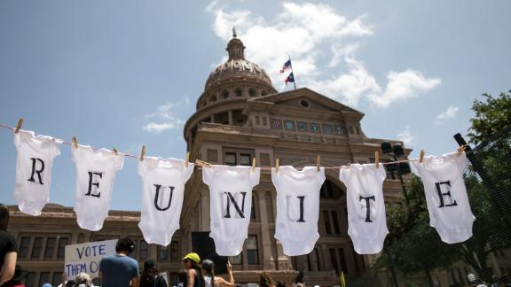 """AUSTIN, TX - JUNE 30: A demonstrator uses baby clothes to spell out the word """"reunite"""" during a rally against the Trump administration"""