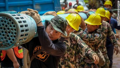 Rescue workers carry  water pumping equipments into Tham Luang Nang Non cave on Sunday.