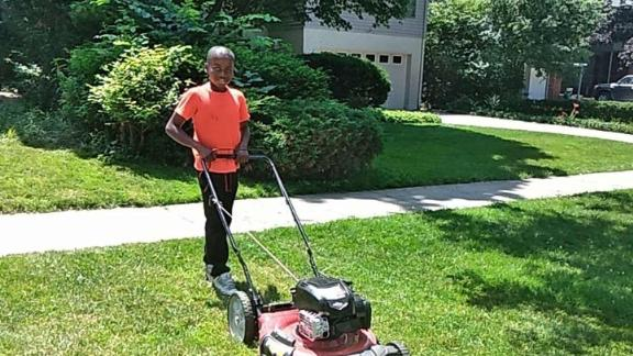 Reggie Fields, 12, mows a lawn on Sunday in Maple Heights, Ohio. His mom says he