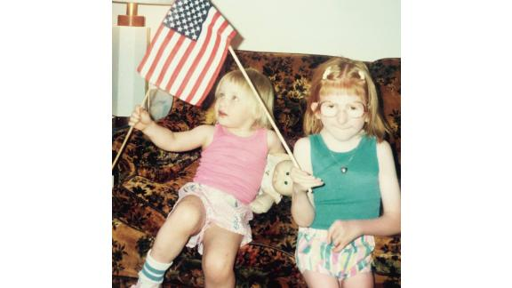 Melissa Blake and her sister wave American flags.