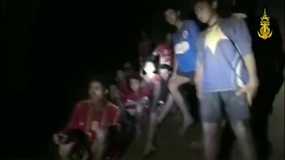 An image of the boys seen perched on a muddy strip deep inside the cave.