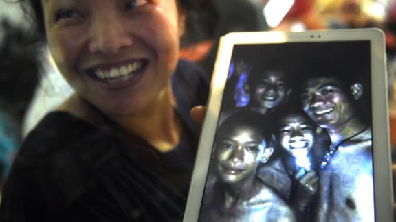 A family member shows a picture of four of the twelve missing boys near the Tham Luang cave at the Khun Nam Nang Non Forest Park in Mae Sai on July 2, 2018.