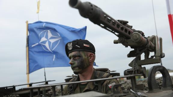 ZAGAN, POLAND - JUNE 18:  A soldier of the Polish Army sits in a tank as a NATO flag flies behind during the NATO Noble Jump military exercises of the VJTF forces on June 18, 2015 in Zagan, Poland. The VJTF, the Very High Readiness Joint Task Force, is NATO