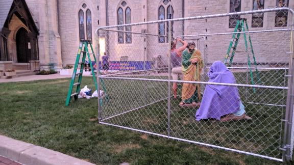 A Christ Church Cathedral volunteer sets up a display of the Holy Family in a cage to protest US immigration policy.
