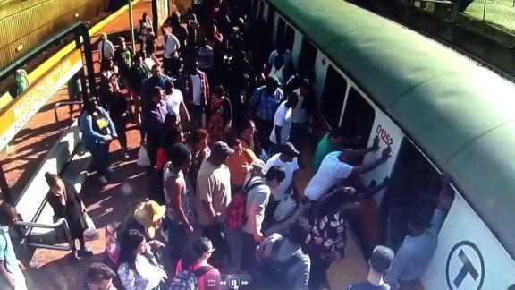 Commuters on Boston's Orange Line rock a subway train to help free a woman whose leg was trapped between the train and the platform.