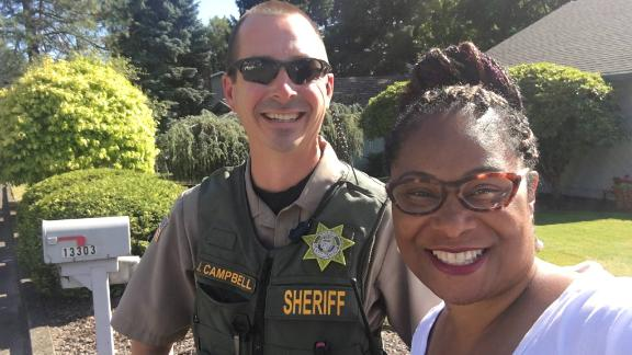 Rep. Janelle Bynum smiles with the officer that was dispatched when a woman called the police on her.