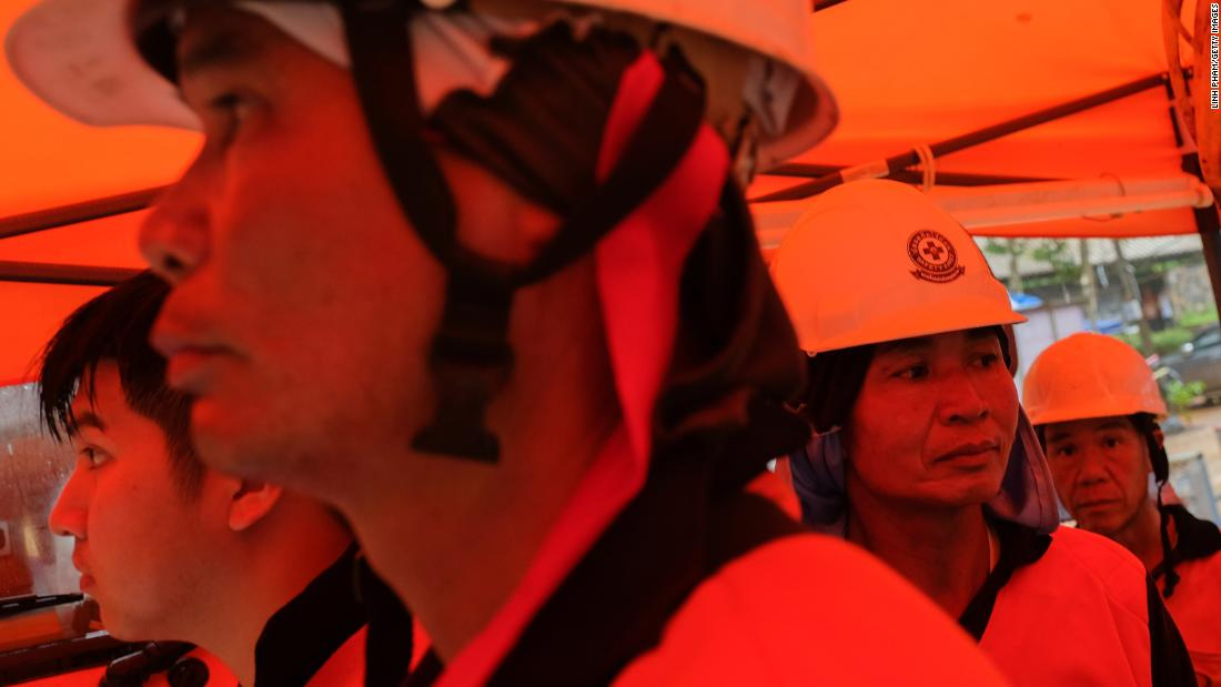 Rescue workers wait at the entrance to the cave on July 2.