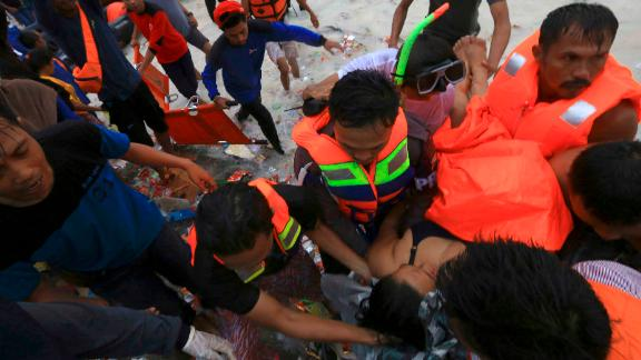 Rescuers remove a passenger from the sinking  KM Lestari Maju ferry.