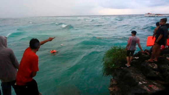 Residents attempt to rescue victims of the sinking ferry Lestari Maju.