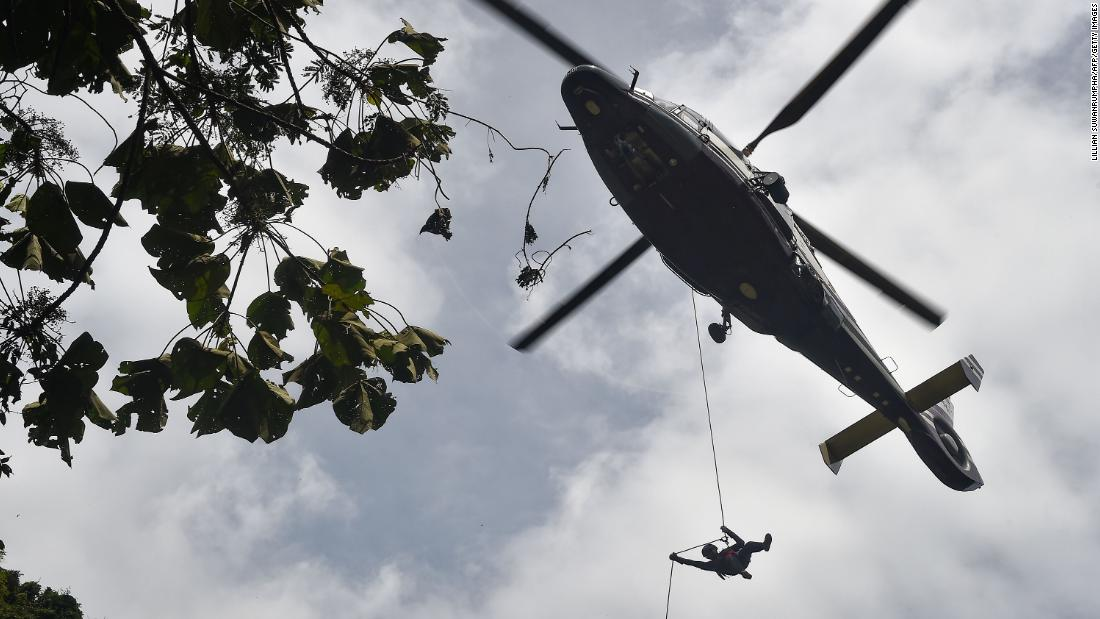 A Thai Air Force worker drops near a possible cave opening on Saturday, June 30.