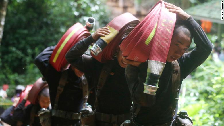 Thai soldiers carry hoses and additional water pumps during the search for the soccer team.