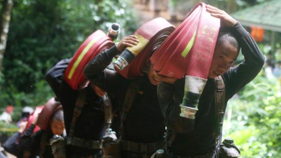 Thai soldiers bring hoses and additional water pumps as the search for the team continued on June 27.