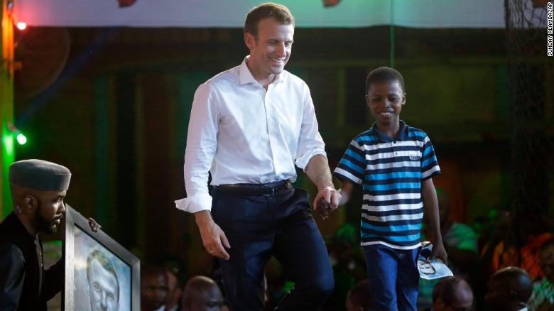 French President Emmanuel Macron, left, walks on stage at the New Africa Shrine in Lagos with 11-year-old, Kareem Waris Olamilekan, a young Nigerian artist who drew his portrait.