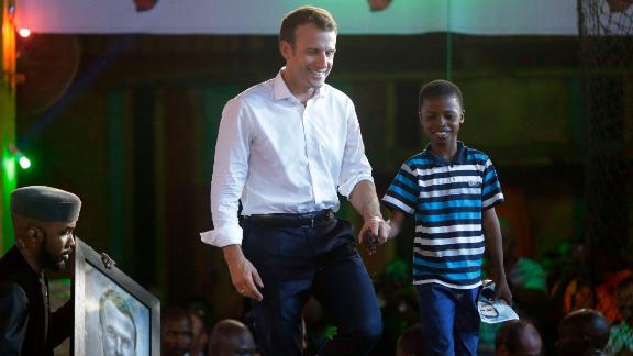 French President Emmanuel Macron, left, walk on the stage with 11 years -old, Kareem Waris Olamilekan,a young Nigerian artist who drew the portrait of President Macron.