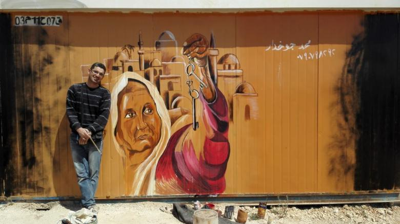 Syrian refugee Mohamed Jokhadar in front of a mural he painted at the Zaatari Camp in Jordan.