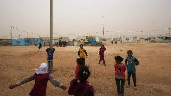 Syrian refugee children play during a sand storm at the Zaatari refugee camp on November 13, 2017.  Some 80,000 Syrian refugees living in the Zaatari camp will have access to 14 hours of electricity per day instead of eight hours, thanks to the opening of the new solar power station. / AFP PHOTO / KHALIL MAZRAAWI        (Photo credit should read KHALIL MAZRAAWI/AFP/Getty Images)