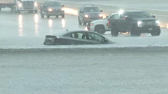 A car is engulfed by water on a Houston road Wednesday.