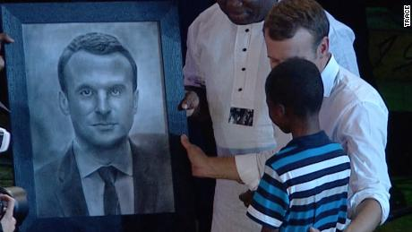 11-year old Nigerian hyperrealist artist, Kareem Olamilekan draws portrait of French President's Macron at the African shrine on July 3, 2018.