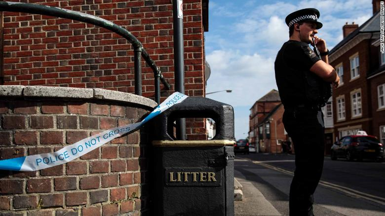 A police officer stands at a cordon around a public trash can Wednesday next to a supported housing project in Salisbury, thought to be connected to the Amesbury victims.