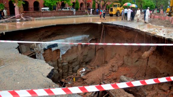 Residents look at a road caved in due to heavy rain fall in Lahore, Pakistan, Tuesday, July 3, 2018. Torrential monsoon rains lashed many cities and towns across Pakistan before dawn Tuesday, flooding streets and killing six people, as authorities struggled to restore normalcy in rain-affected areas. (AP Photo/K.M. Chaudary)