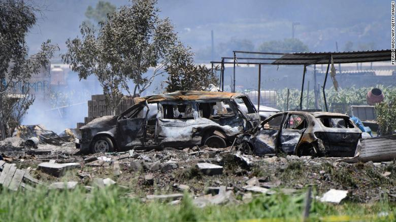 Charred vehicles remain at the site of explosions at warehouses in Tultepec.