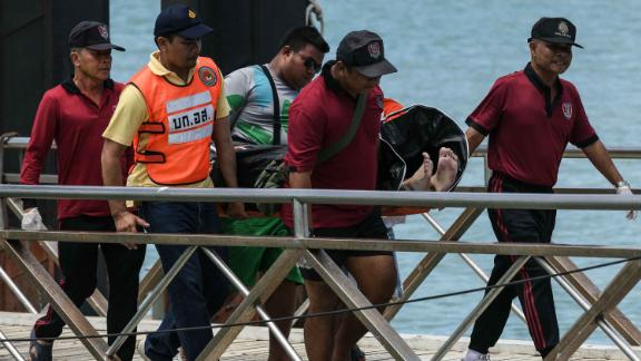 Thai rescue personnel carry one of the deceased passengers recovered from the capsized tourist boat.