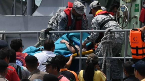 Rescue personnel carry an injured passenger on a stretcher.