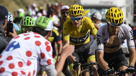 Chris Froome (in yellow) rides uphill through crowds of fans during the 2017 Tour de France.