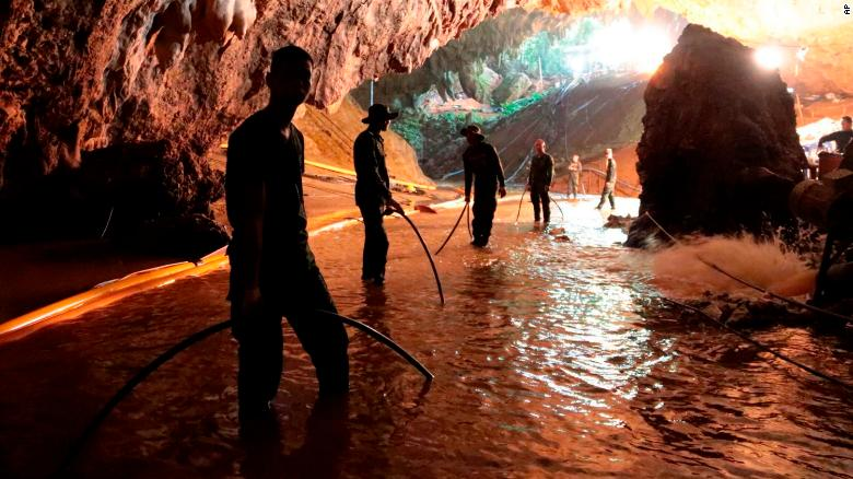 Thai rescue teams arrange a water pumping system at the entrance to a flooded cave complex where 12 boys and their soccer coach have been trapped since June 23, in Mae Sai, Chiang Rai province, northern Thailand on Saturday, July 7, 2018.