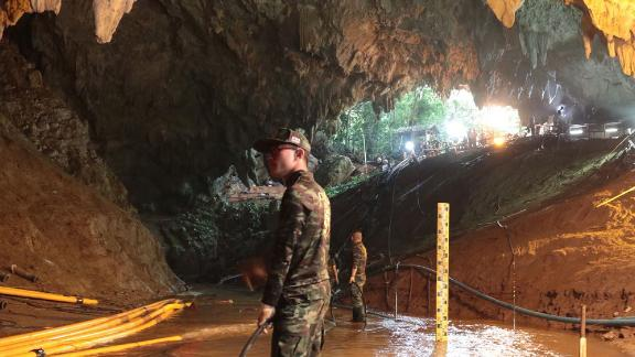 Military personnel work inside a cave.