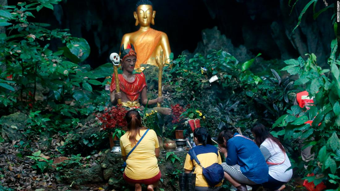 Family members pray in front of a Buddhist statue near the cave on July 8.