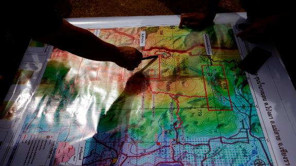 Thai forest rangers examine a map as they review their rescue options on July 8.