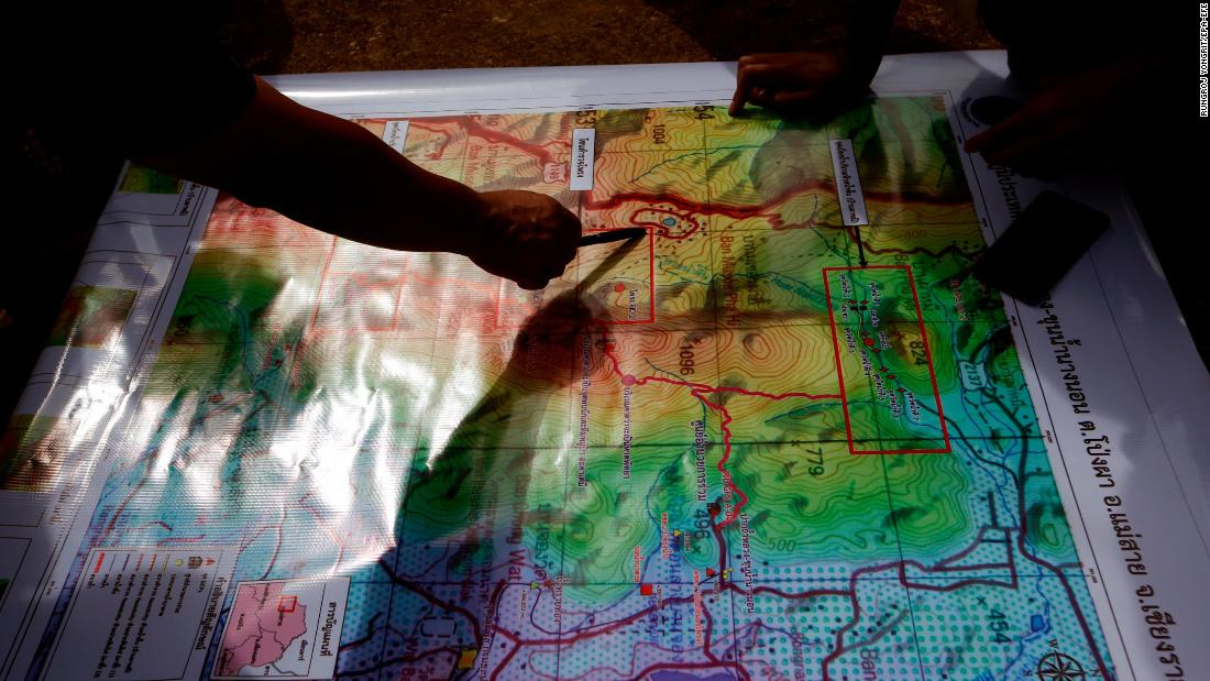 Thai forest rangers examine a map as they review their options during the ongoing rescue operations Saturday.