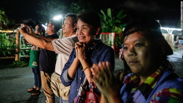 Onlookers watch and cheer as ambulances deliver boys rescued from a cave in northern Thailand to hospital in Chiang Rai, Thailand, after they were transpored by helicopter on July 8, 2018.
