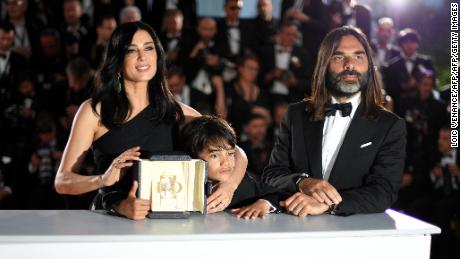 "TOPSHOT - Lebanese director and actress Nadine Labaki (L), her husband Lebanese producer Khaled Mouzanar (R) and Syrian actor Zain al-Rafeea pose with the trophy on May 19, 2018 during a photocall after Labaki won the Jury Prize for the film ""Capharnaum"" at the 71st edition of the Cannes Film Festival in Cannes, southern France. (Photo by Loic VENANCE / AFP)        (Photo credit should read LOIC VENANCE/AFP/Getty Images)"