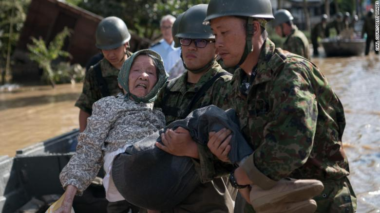 Soldiers carry an elderly woman away from flood water on July 8, 2018 in Kurashiki near Okayama, Japan.