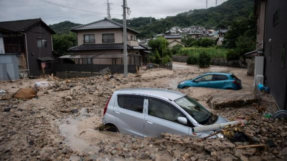 TOPSHOT - A picture shows cars trapped in the mud after floods in Saka, Hiroshima prefecture on July 8, 2018. - Japan