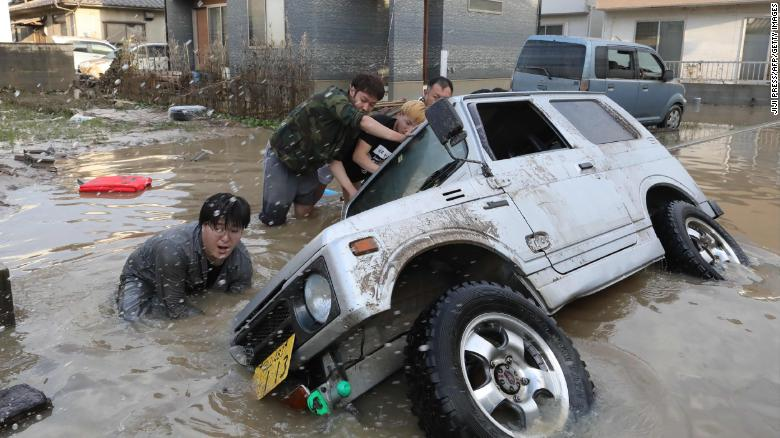 Residents try to upright a vehicle stuck in a flood hit area in Kurashiki, Okayama prefecture on July 9, 2018.
