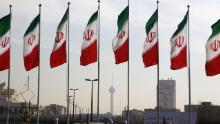 Tehran's landmark Milad Tower is seen through a row of national flags in the center of the Iranian capital on January 3, 2018.