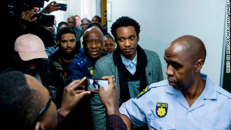 Duduzane Zuma (2R), son of former South African president Jacob Zuma, leaves a Johannesburg court, where he faced corruption charges before being released on bail on July 9, 2018.