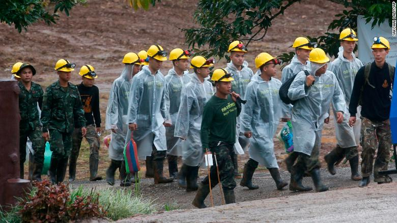Rescuers walk toward the entrance of the cave where four boys and their coach are still trapped, as rescue operations resume on Tuesday morning, July 10.