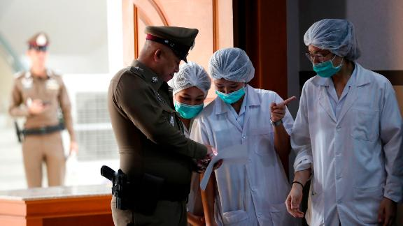 Hospital staff and a police officer are seen during a news conference that was held on July 10. The eight boys that had been rescued on July 8 and 9 were being treated in an isolation ward in a Chiang Rai hospital.